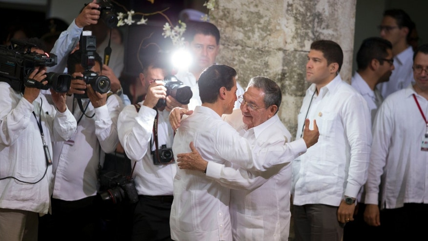 Mexican President Enrique Pena Nieto, center left, hugs Cuban President Raul Castro as Castro arrives for his welcome ceremony at the Yucatan state government palace in Merida, Mexico, Friday, Nov. 6, 2015. Among the agreements to be signed between their nations is a memorandum of understanding to guarantee the legal, orderly and safe flow of migration between the two countries. (AP Photo/Rebecca Blackwell)