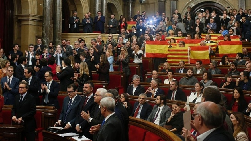 Popular Party of Catalonia members, right, show Spanish flags and Catalonia flags at the end of a parliamentary session at the Parliament in Barcelona, Spain, Monday, Nov. 9, 2015. The regional parliament of northeastern Catalonia is due to vote on a proposal by secessionist parties that hold a majority in the chamber to set up a road map for independence from Spain by 2017. The initiative defies Spain's central government, which considers it unconstitutional. (AP Photo/Manu Fernandez)