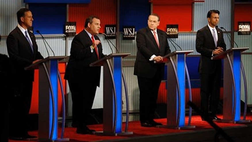 Chris Christie, second from left, speaks as Rick Santorum, left, Mike Huckabee and Bobby Jindal look on during Republican presidential debate at Milwaukee Theatre, Tuesday, Nov. 10, 2015, in Milwaukee. (AP Photo/Morry Gash)