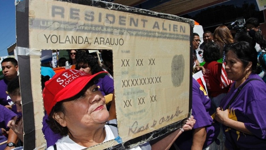 April 10, 2013: Protester Yolanda Araujo holds a mock resident alien card at a rally for immigration reform near Senator Dianne Feinstein's office, in Los Angeles, California. (Reuters)