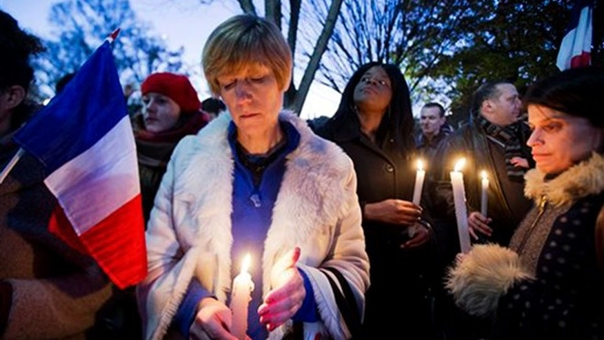Alexandra Salomon, from Paris, France, center, joins a vigil outside the White House in Washington, Saturday, Nov. 14, 2015, to pay tribute to the victims of the Paris attacks. Multiple attacks across Paris on Friday night have left scores dead and hundreds injured. (AP Photo/Manuel Balce Ceneta)