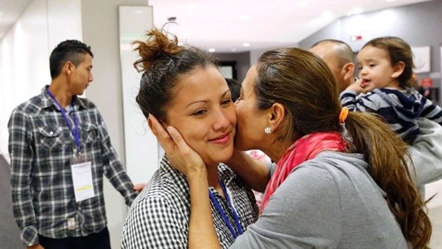 In this Nov. 12, 2015, photo, Wendy Mejia, 16, hugs her aunt after her arrival from El Salvador at Baltimore-Washington International Airport in Linthicum, Md. After 15 years apart, Wendy and her brother Brian reunited with their parents, becoming among the first teenagers to be granted refugee status and permission to travel legally to the United States through the State Department's Central American Minor program. (AP Photo/Patrick Semansky)