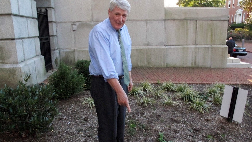 Nov. 20, 2015: Maryland House Speaker Michael Busch points to a weed on the grounds of the Maryland State House in Annapolis, Md.
