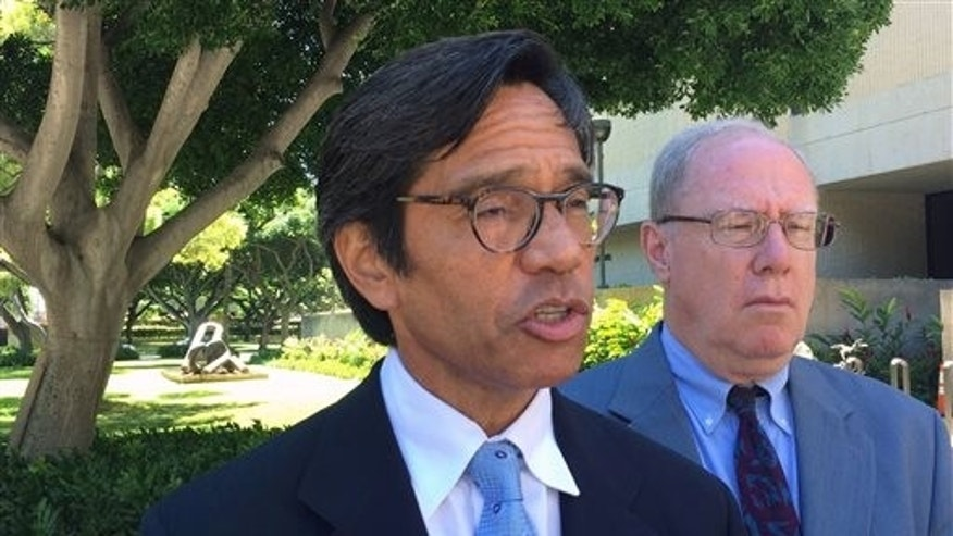 FILE - In a Friday, Oct. 23, 2015 file photo, Bill Meheula, left, an attorney for Nai Aupuni, speaks to reporters outside U.S. District Court in Honolulu. A U.S. Supreme Court justice on Friday issued a temporary stay blocking the counting of votes in an election that would be a significant step toward Native Hawaiian self-governance. Justice Anthony Kennedy's order also stops the certification of any winners pending further direction from him or the entire court. (AP Photo/Audrey McAvoy, File)