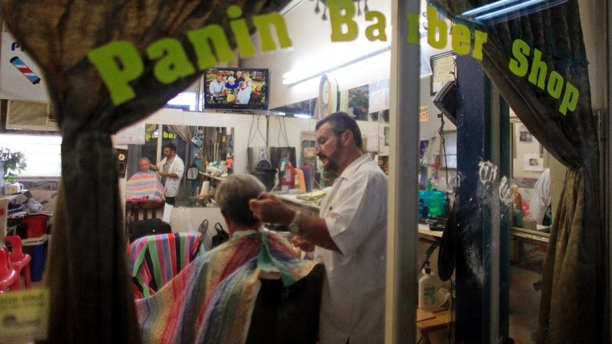In this Sept. 2, 2015 photo, Francisco Gonzalez gives a haircut to a customer at his barbershop in Lares, Puerto Rico. Despite the economic downturn, some business owners are determined to stick it out in Lares. (AP Photo/Ricardo Arduengo)
