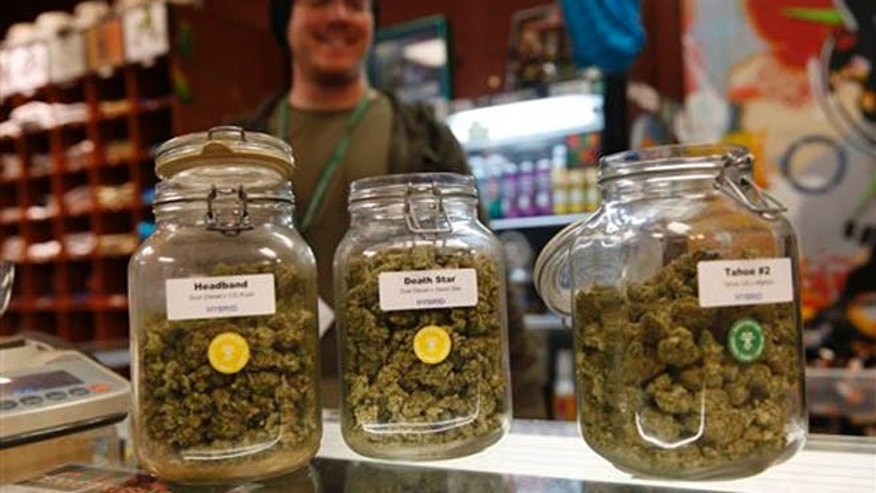 Jars of marijuana buds sit on the counter at the Denver Kush Club early Friday, Nov. 27, 2015, in north Denver. More than two dozen customers took advantage of a new Colorado holiday tradition of marijuana shops drawing customers with discounted weed and holiday gift sets. (AP Photo/David Zalubowski)