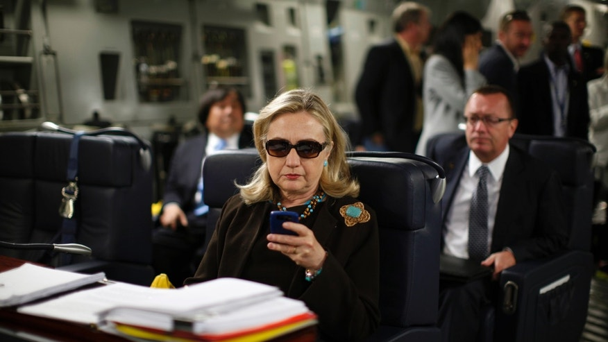 U.S. Secretary of State Hillary Rodham Clinton works from a desk inside a C-17 military plane upon her departure from Malta, in the Mediterranean Sea, bound for Tripoli, Libya, Tuesday Oct.18, 2011.