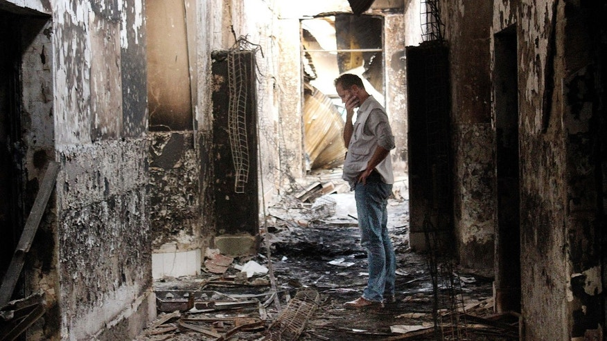 FILE - In this Friday, Oct. 16, 2015 file photo, an employee of the Doctors Without Borders hospital looks at damages after a U.S. airstrike hit in Kunduz, Afghanistan.