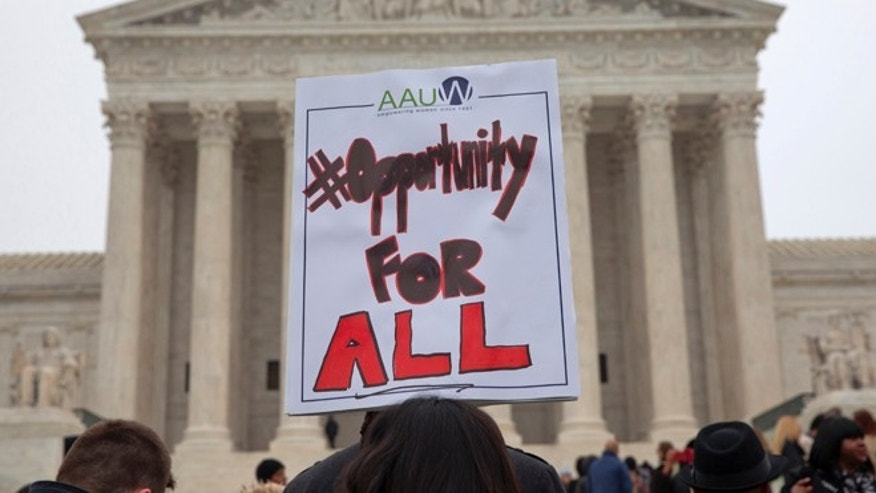 Pamela Yuen, with the American Association of University Women, holds a sign in favor of affirmative action outside of the Supreme Court in Washington, Wednesday, Dec. 9, 2015, as the court hears oral arguments in the Fisher v. University of Texas at Austin affirmative action case. (AP Photo/Jacquelyn Martin)