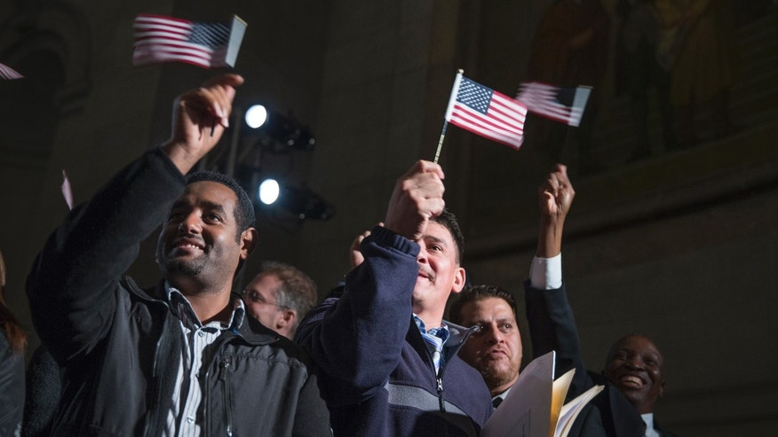 "Participants in a naturalization ceremony wave flags after taking the ""Oath of Allegiance"" at an event attended by President Barack Obama at the National Archive in Washington, Tuesday, Dec. 15, 2015. The president spoke at the National Archives Museum, where 31 immigrants from Iraq, Ethiopia, Uganda and 23 other nations are being sworn in as U.S. citizens. (AP Photo/Evan Vucci)"