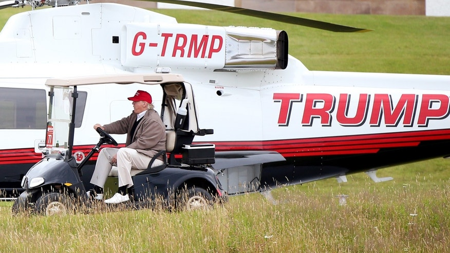 July 31, 2015: US presidential contender Donald Trump drives his golf buggy past his helicopter during the second day of the Women's British Open golf championship on his Turnberry golf course in Turnberry, Scotland.