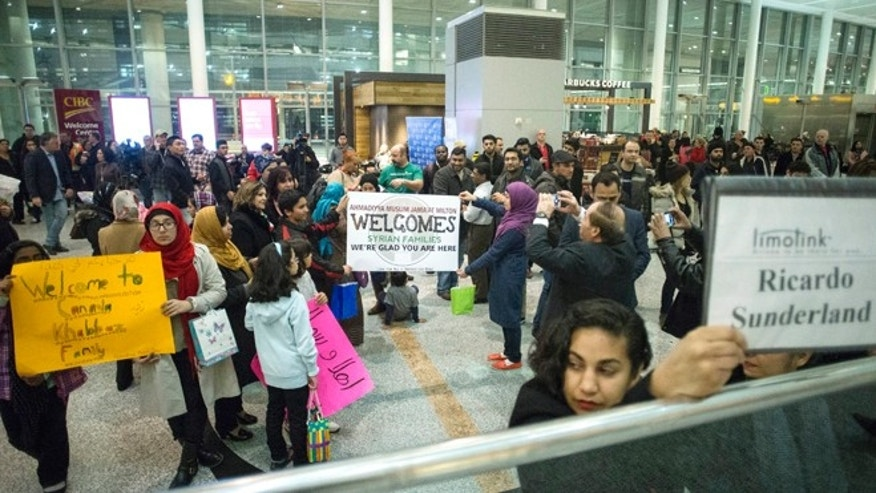 Members of groups who are sponsoring two Syrian refugee families hold up signs welcoming their charges as they wait for the families to arrive at Toronto Pearson International Airport, Wednesday, Dec. 9, 2015, Mississauga, Ontario, Canada. (Chris Young/The Canadian Press via AP) MANDATORY CREDIT