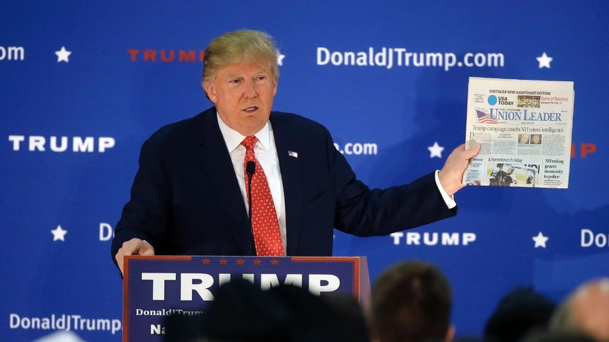 Dec. 28, 2015: Republican presidential candidate Donald Trump displays a copy of the Union Leader newspaper while addressing an audience during a campaign event.