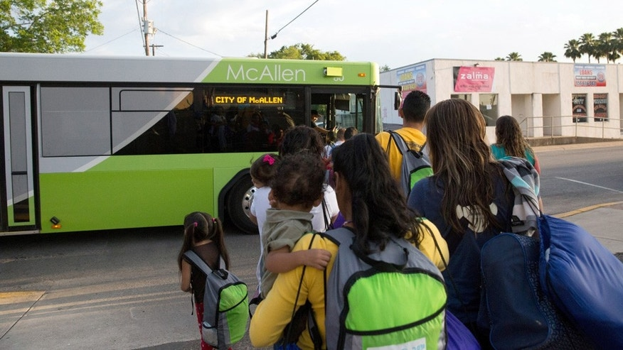 FILE - In this file photo from April 30, 2015, immigrant families, many of them mothers with children, board a bus headed to the downtown bus station in McAllen, Texas. (AP Photo/Seth Robbins, File)