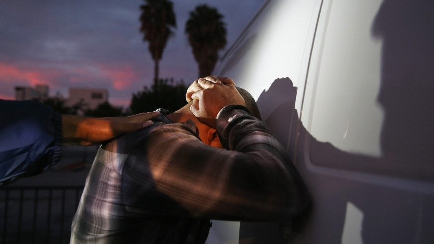 A man is detained by Immigration and Customs Enforcement (ICE), agents early on October 14, 2015 in Los Angeles, California. (Photo by John Moore/Getty Images)