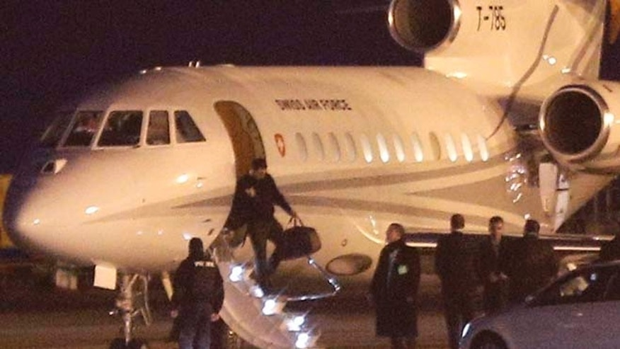 An unidentified man leaves a Dassault Falcon jet of Swiss air force at the airport in Geneva, Switzerland, Sunday, Jan 17, 2016. A US government plane waited nearby to bring back to the US the men who were left from imprisonment in Iran the day before. (AP Photo/Laurent Cipriani)
