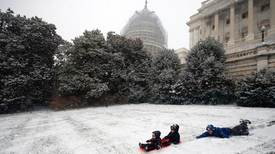 Friday, Jan. 22, 2016: Ben Cichy and his son Adrian, 18 months, and Logan 3, sled in the snow on Capitol Hill, in Washington, D.C. (AP)
