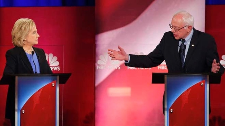 Democratic presidential candidate, Sen. Bernie Sanders, I-Vt.,  gestures towards Democratic presidential candidate, former Secretary of State Hillary Clinton during a democratic presidential primary debate at the Gaillard Center, Sunday, Jan. 17, 2016, in Charleston, S.C. (AP Photo/Mic Smith)