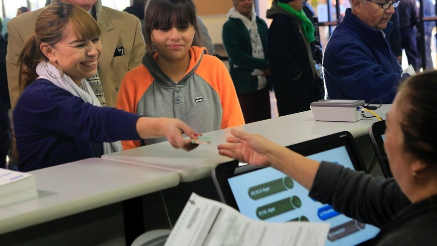 GRANADA HILLS, CA - JANUARY 2, 2015:  Sonia Soriano, left, with daughter Kelya, 12, right, was first in line to fill out paperwork for her California driver license at DMV offices January 2, 2015 in Granada Hills.  (Photo by Brian van der Brug/Los Angeles Times via Getty Images)