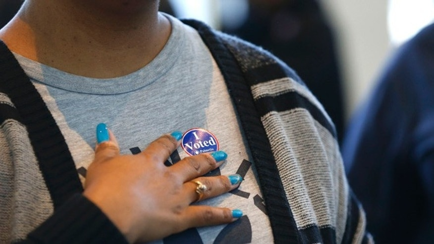 A voter places a sticker on her chest after voting in the South Carolina Democratic primary at a polling place at Sanders Middle School in Columbia, S.C., Saturday, Feb. 27, 2016. (AP Photo/Gerald Herbert)