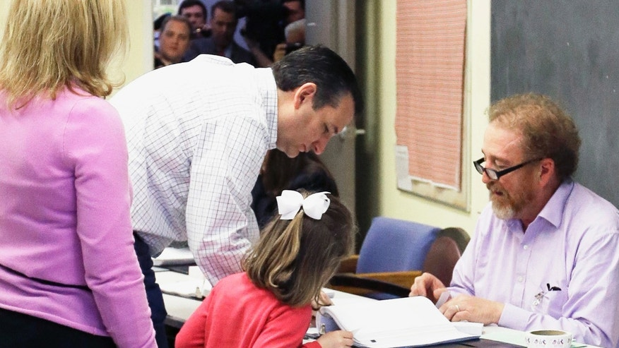 Republican presidential candidate, Sen. Ted Cruz, R-Texas, center, accompanied by his daughter, signs in at a polling place to vote in the Texas primary,Tuesday, March 1, 2016, in Houston. (AP Photo/Pat Sullivan)