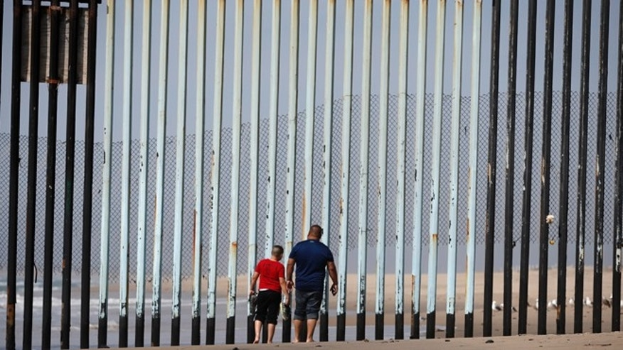 Two people walk towards metal bars marking the United States border where it meets the Pacific Ocean Wednesday, March 2, 2016, in Tijuana, Mexico. (AP Photo/Gregory Bull)