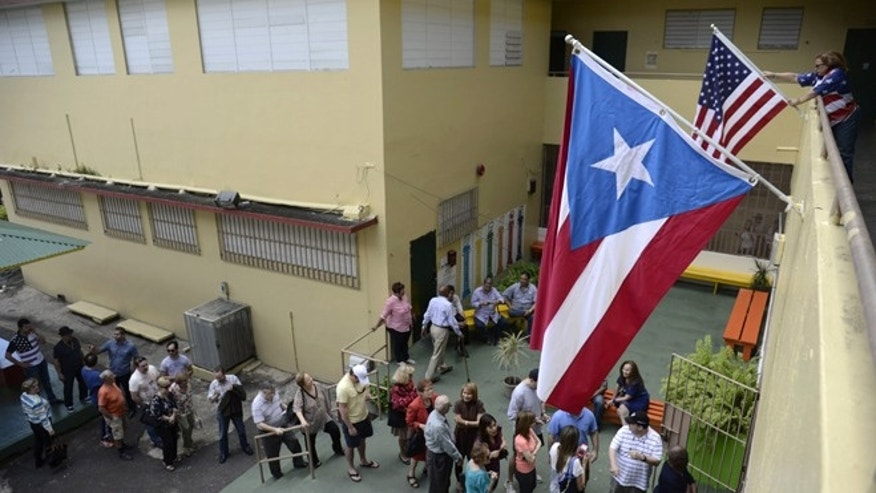 Puerto Rico's resident line up to vote during the U.S. territory's Republican primary at the Santurce county in San Juan, Puerto Rico, Sunday March 6, 2016 . Puerto Rico residents cannot participate in general presidential elections but can do so in primaries. Puerto Rico sends 20 delegates to the Republican convention.(AP Photo/Carlos Giusti)