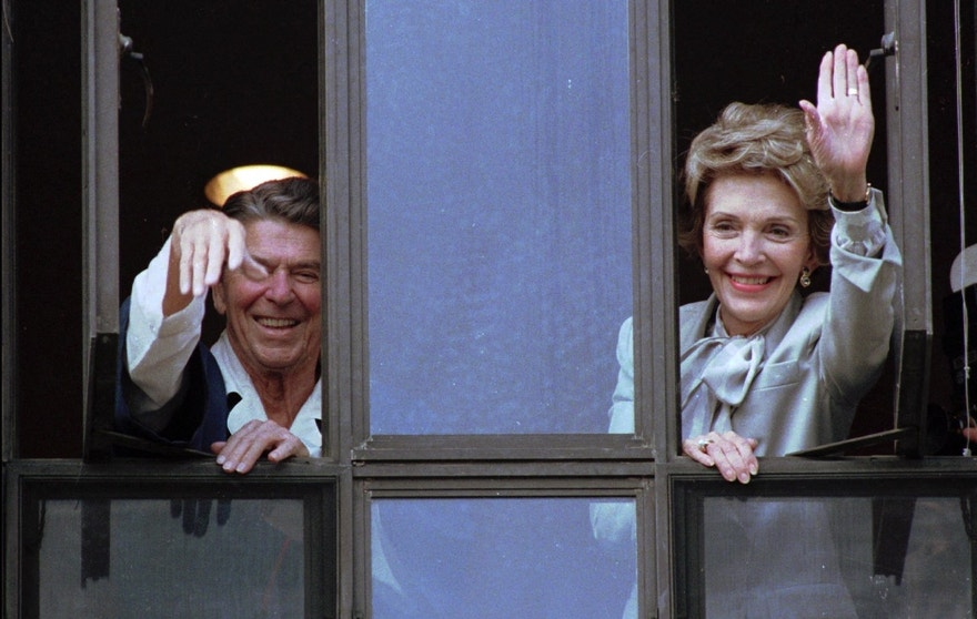 FILE - In this July 18, 1985, file photo, President Ronald Reagan and his wife, Nancy, wave from windows of his hospital room at the Navy Medical Center in Bethesda, Md. The former first lady has died at 94, The Associated Press confirmed Sunday, March 6, 2016. (AP Photo/Scott Stewart, File)
