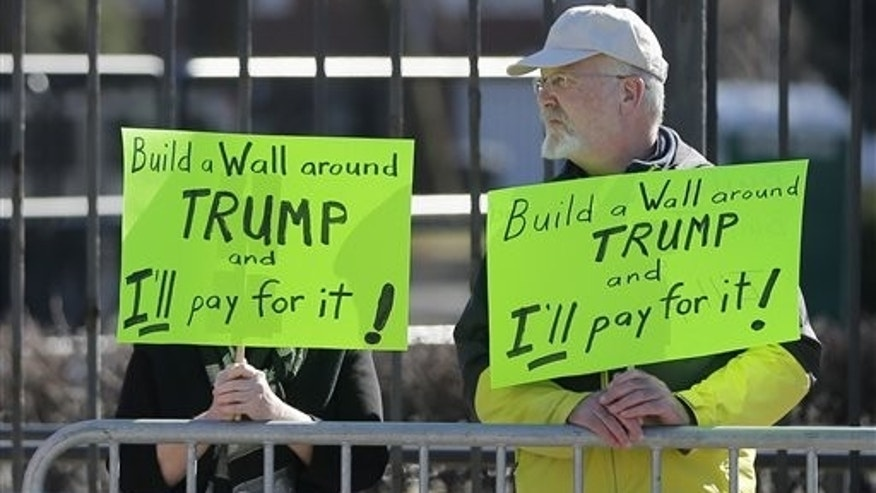 Two protesters of Republican presidential candidate, Donald Trump stand outside on the University of Illinois-Chicago campus before a Trump rally,, Friday, March 11, 2016, in Chicago. (AP Photo/Charles Rex Arbogast)
