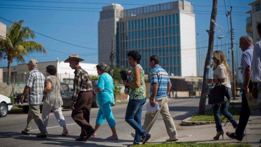 Jan. 13, 2014: People walk in line while entering the U.S. Interests Section to apply for U.S. travel visas in Havana.