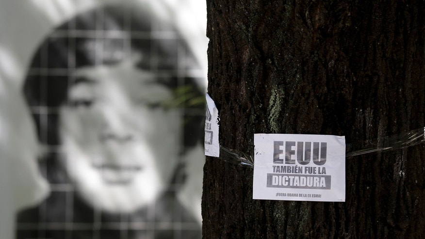 "March 16, 2016: A picture of a person that was disappeared during Argentina's military dictatorship is seen behind a leaflet on a tree that reads in Spanish ""The U.S. was also the dictatorship, Obama out of former Argentine Navy School of Mechanics"" at the Space for Memory and for the Promotion and Defense of Human Rights in Buenos Aires. (AP Photo/Natacha Pisarenko)"