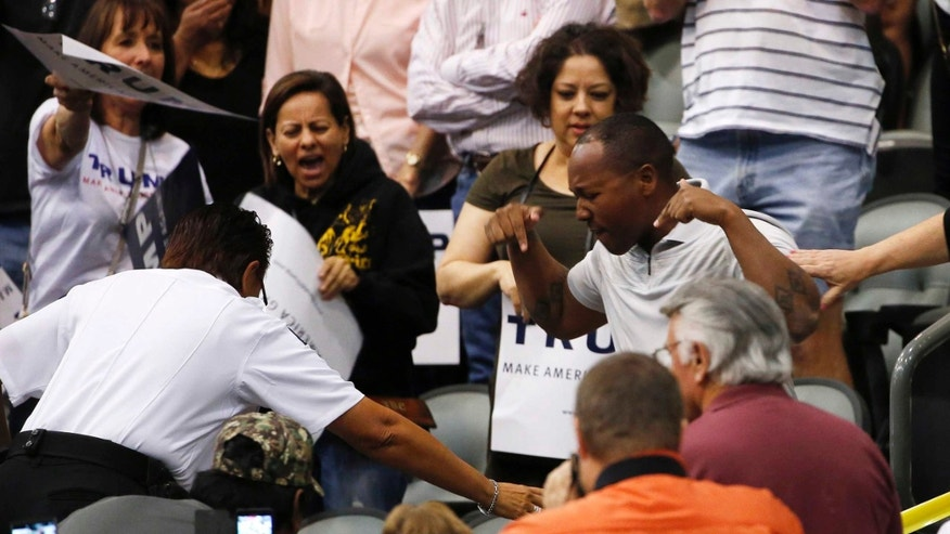 A supporter of Republican presidential candidate Donald Trump, right, shouts and gestures to a protester, on the ground and not seen, as they scuffle as Trump speaks during a campaign rally Saturday, March 19, 2016, in Tucson, Ariz. (AP Photo/Ross D. Franklin)