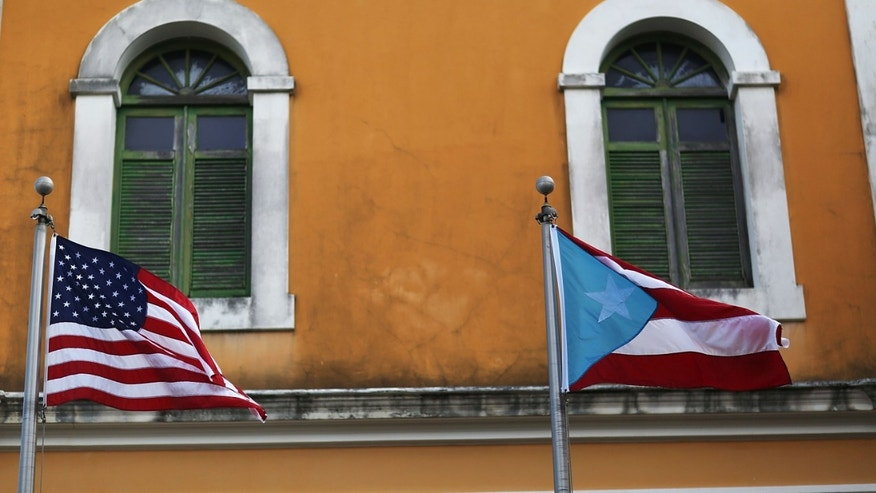 An American flag and Puerto Rican flag fly next to each other in Old San Juan.