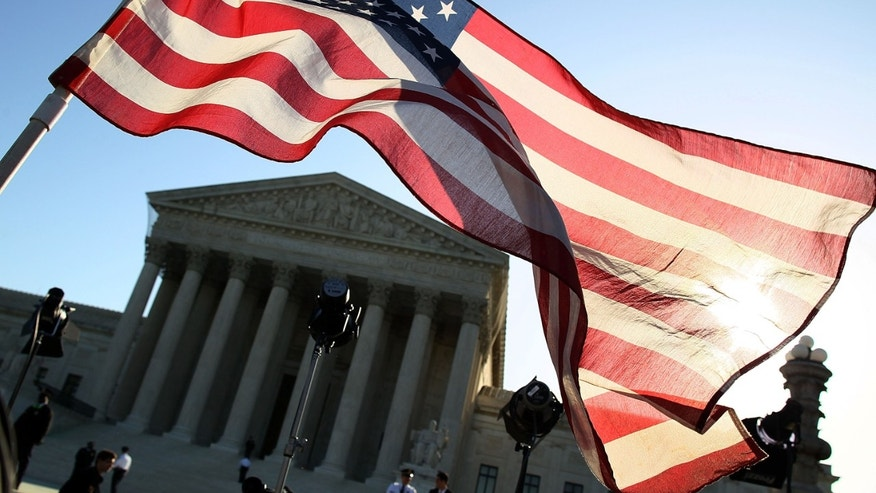 WASHINGTON, DC - MARCH 26:  A person carries an American flag while marching in favor of the Patient Protection and Affordable Care Act in front of the U.S. Supreme Court on March 26, 2012 in Washington, DC. Today the high court, which has set aside six hours over three days, will hear arguments over the constitutionality President Barack Obama's Patient Protection and Affordable Care Act.   (Photo by Mark Wilson/Getty Images)