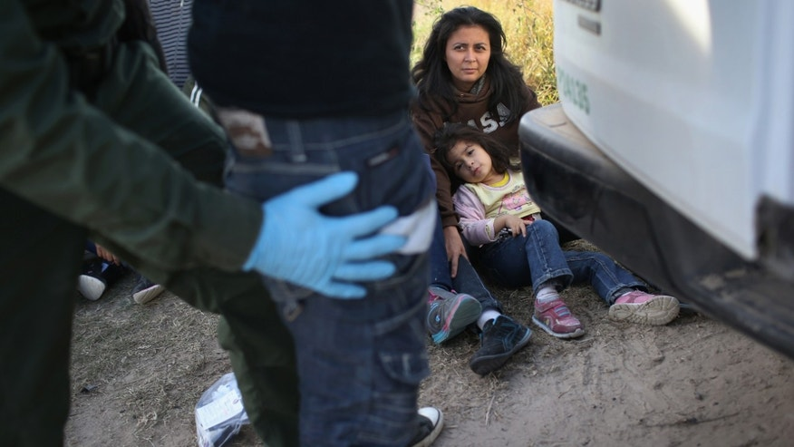 RIO GRANDE CITY, TX - DECEMBER 08:  Central American immigrants wait to be transported after turning themselves in to U.S. Border Patrol agents on December 8, 2015 near Rio Grande City, Texas. They had just illegally crossed the U.S.-Mexico border into Texas to seek asylum. The number of migrant families and unaccompanied minors has again surged in recent months, even as the total number of illegal crossings nationwide has gone down over the previous year.  (Photo by John Moore/Getty Images)
