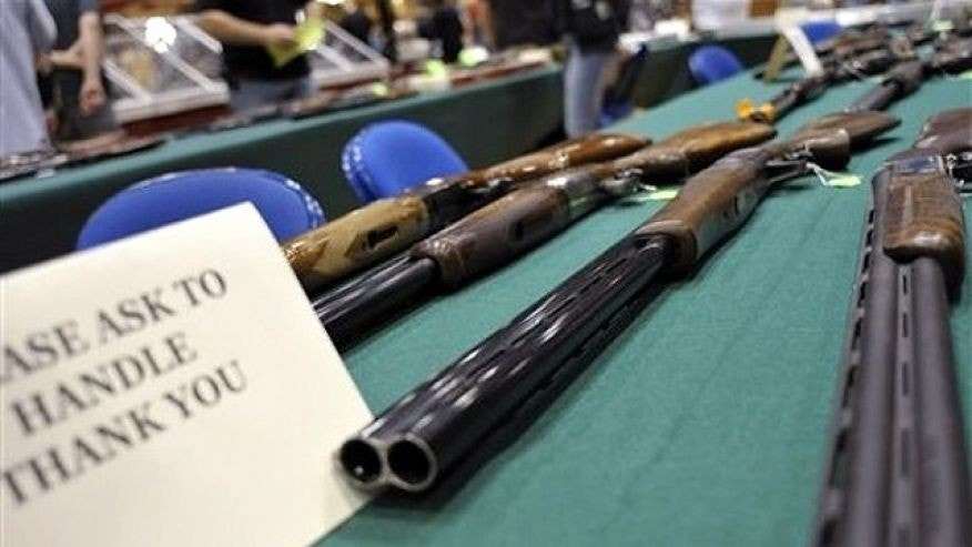 June 19, 2010: Assorted shotguns are displayed on a table at a gun and knife show in White Plains, N.Y.