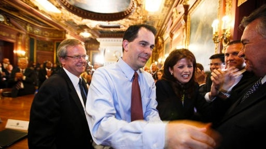In this June 6, 2012 file photo, Wisconsin Gov. Scott Walker, second from left, and Lt. Gov. Rebecca Kleefisch are greeted by the governor's cabinet and staff at the state Capitol Madison, Wis., a day after Walker beat Milwaukee Mayor Tom Barrett in a recall election. (AP)