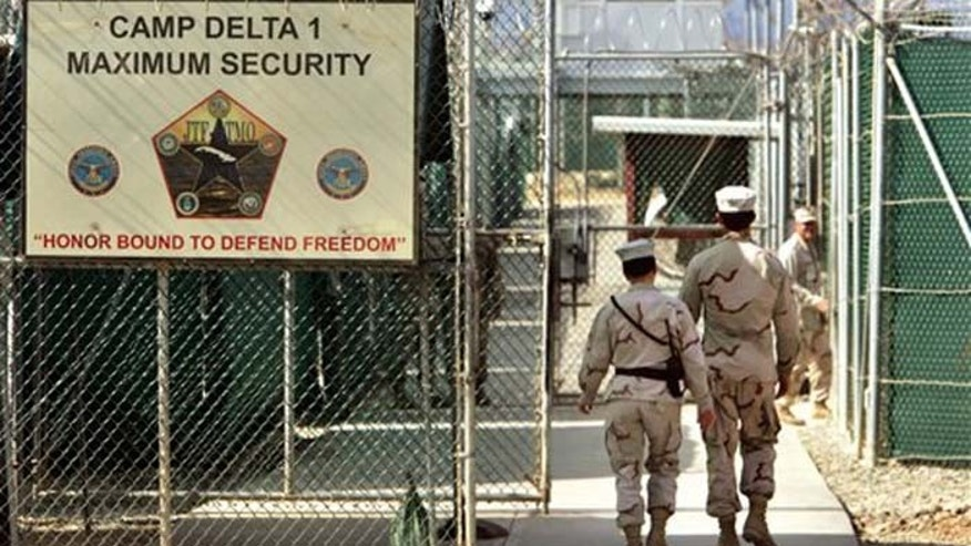 FILE - In this June 27, 2006 file photo, reviewed by a U.S. Department of Defense official, U.S. military guards walk within Camp Delta military-run prison, at the Guantanamo Bay U.S. Naval Base, Cuba. A senior U.S. official says the first of 17 detainees scheduled to be released from the Guantanamo Bay prison in January will be transferred next week, as the Obama administration continues efforts to reduce the population at the controversial detention center.  (AP Photo/Brennan Linsley, File)