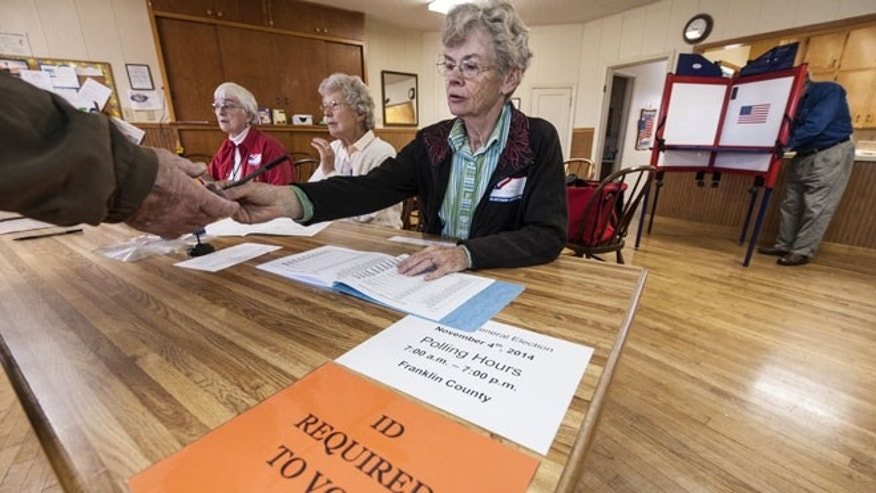 CENTROPOLIS TOWNSHIP, KS -  NOVEMBER 4: Election worker Karen Witham checks voter identifications in the Richter Church November 4, 2014 in Centropolis Township, near Ottawa, Kansas. A tight race between independent candidate, Greg Orman (I-KS) and U.S. Sen. Pat Roberts (R-KS) brought voters to the polls in the Kansas midterm elections. (Photo by Julie Denesha/Getty Images)
