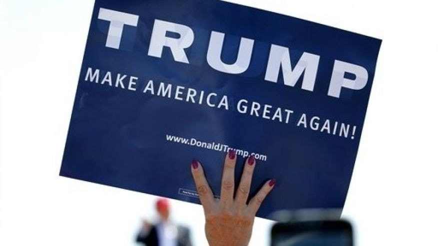 In this March 19, 2016 file photo, a supporter holds a sign as Republican presidential candidate Donald Trump speaks during a campaign rally in Fountain Hills, Ariz.