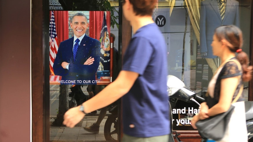 "May 22, 2016: A Vietnamese couple pass a poster of U.S President Barrack Obama with footnote read ""Welcome to our city"", hanging in a door front in Hanoi, Vietnam."