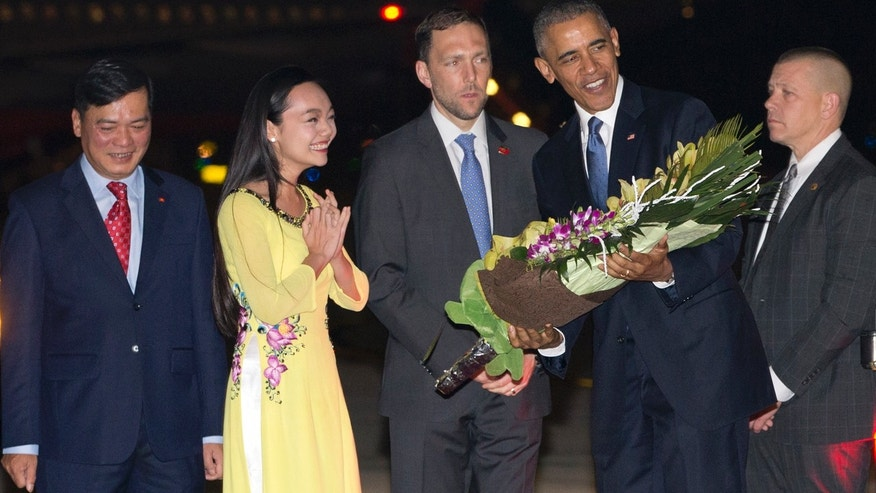 May 22, 2016: President Barack Obama is given flowers by Linh Tran, the ceremonial flower girl, as he arrives on Air Force One at Noi Bai International Airport in Hanoi, Vietnam.