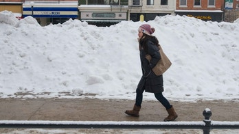 IOWA CITY, IOWA - FEBRUARY 22:  A University of Iowa student walks past a snowbank after a winter storm left more than six  inches of snow on February 22, 2013  in Iowa City, Iowa. The winter blizzard continues to move across the entire midwest, dumping up to a foot of snow in places as it moves east. (Photo by David Greedy/Getty Images)