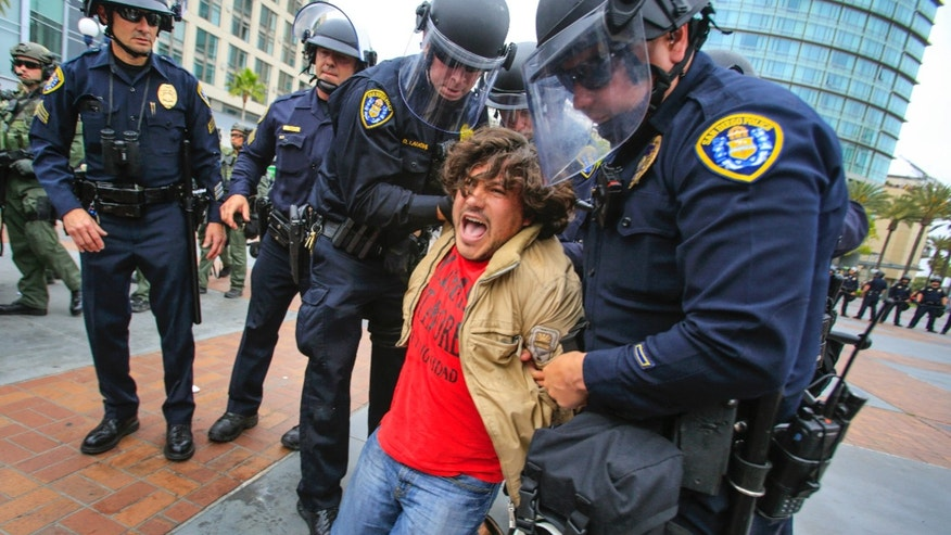 May 27, 2016: San Diego police officers in full riot gear arrest an anti Trump demonstrator near 5th Avenue and Harbor Drive in the Gaslamp Quarter after Republican presidential candidate Donald Trump held a rally at the San Diego Convention Center .