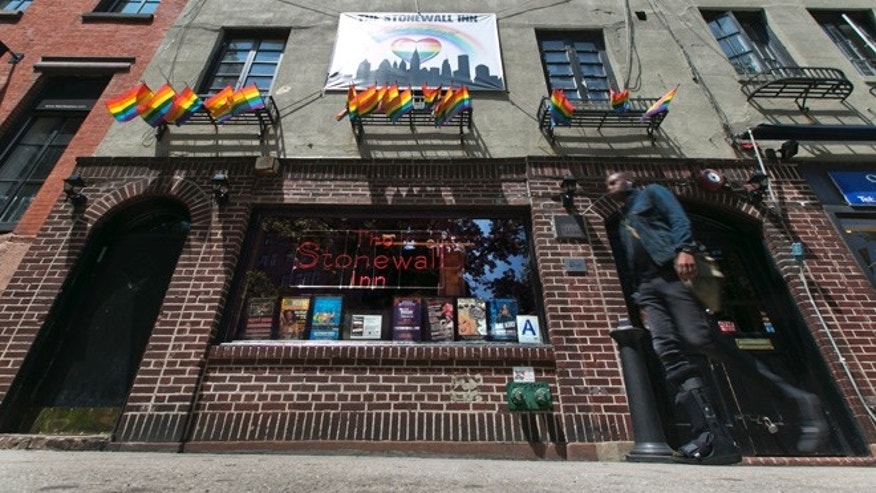 FILE - In this May 29, 2014 file photo, a man passes The Stonewall Inn in New York's Greenwich Village. President Barack Obama is designating the Stonewall Inn in New York a national monument, the first to honor gay rights. (AP Photo/Richard Drew, File)