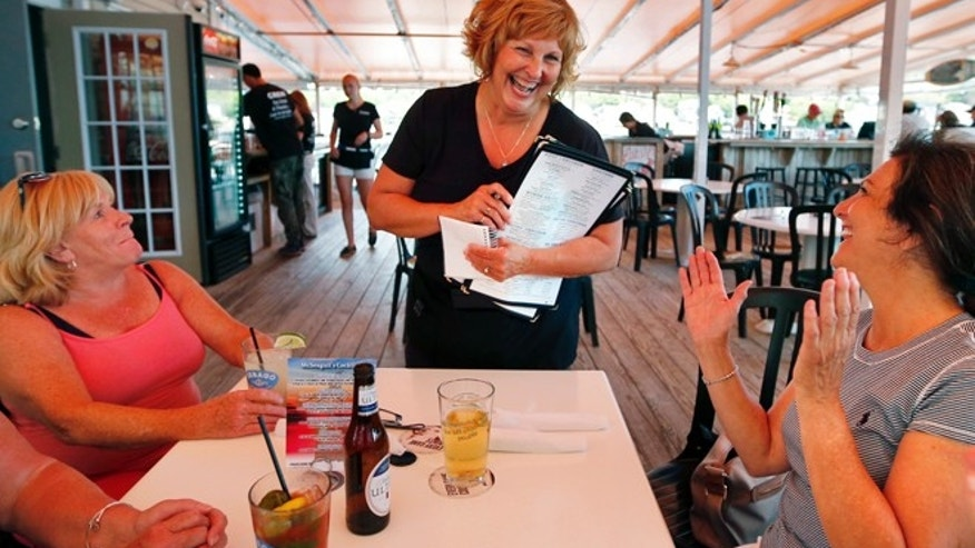 June 23, 2016: Ann LePage chats with diners after taking their order at McSeagull's restaurant in Boothbay Harbor, Maine. (AP)