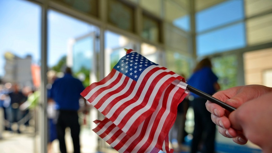 A volunteer passes out American flags to supporters before GOP presidential candidates speak at a forum sponsored by Heritage Action at the Bon Secours Wellness Arena, Friday, Sept. 18, 2015, in Greenville, S.C. (AP Photo/Richard Shiro)