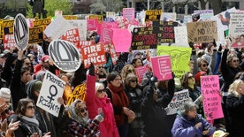 In this April 9, 2016 file photo,  hundreds of abortion rights supporters gather at the Indiana Statehouse in Indianapolis to protest an anti-abortion law signed by Gov. Mike Pence, that is among the most restrictive in the U.S. A federal judge weighing whether to block a new Indiana law mandating that aborted fetuses be buried or cremated and also banning abortions sought because of a fetus' genetic abnormalities will hear Tuesday, June 14, 2016,  from attorneys for the measure's supporters and opponents. (Mykal McEldowney/The Indianapolis Star via AP) NO SALES; MANDATORY CREDIT