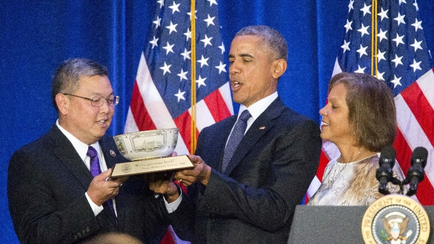 FILE - In this Jan. 28, 2016 file photo, President Barack Obama, center, is presented a commemorative bowl from Rep. Mark Takai, D- Hawaii, left, and Rep. Robin Lynne Kelly, D-N.Y., right, before speaking at the House Democratic Issues Conference in Baltimore, Md. Takai died at his home on Wednesday, July 20, 2016 after battling cancer. (AP Photo/Pablo Martinez Monsivais, file)