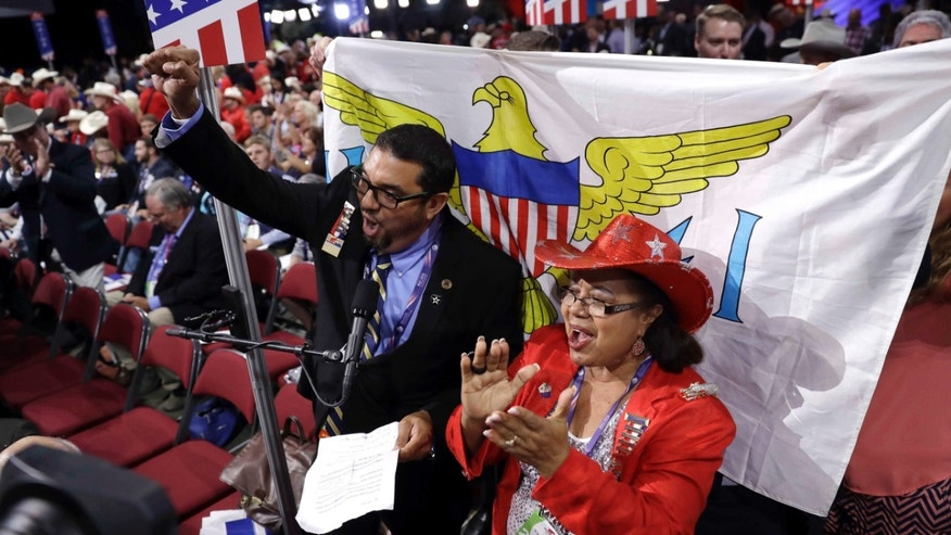 Virgin Islands delegates John Canegate and Lillian Belardo de O'Neal cheer during the second day session of the Republican National Convention in Cleveland, Tuesday, July 19, 2016. (AP Photo/Matt Rourke)
